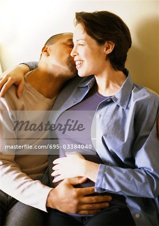 Pregnant woman sitting with arm around man, portrait Stock Photo - Premium Royalty-Free, Image code: 695-03384040