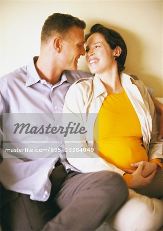 Man and pregnant woman sitting and smiling at each other Stock Photo - Premium Royalty-Free, Image code: 695-03384049