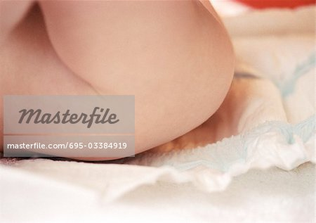 Baby having diaper changed, mid-section, side view, close-up Stock Photo - Premium Royalty-Free, Image code: 695-03384919