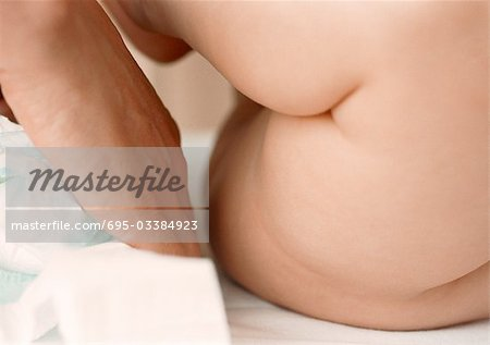 Baby having diaper changed, mid-section, side view, close-up Stock Photo - Premium Royalty-Free, Image code: 695-03384923
