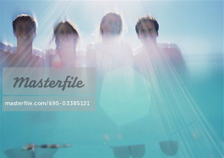 Two men and two women, low angle view, shot from underwater Stock Photo - Premium Royalty-Free, Image code: 695-03385121