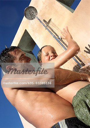 Man holding child in shower. Stock Photo - Premium Royalty-Free, Image code: 695-03385136