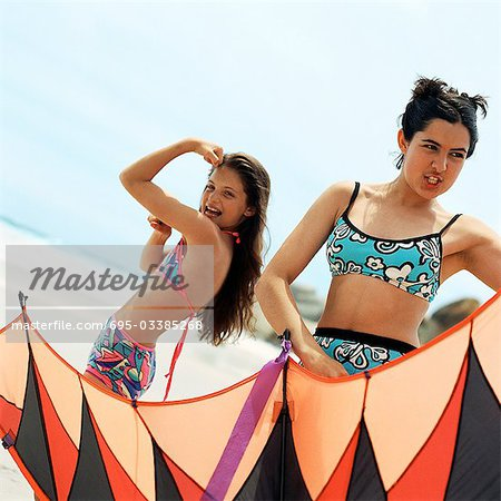 Girl in bathing suit flexing arm muscles, teenager holding kite at the beach Stock Photo - Premium Royalty-Free, Image code: 695-03385268