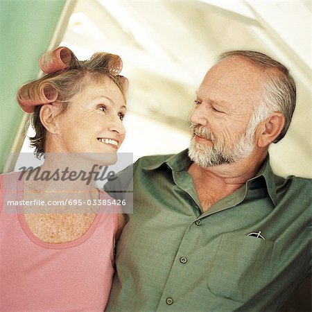 Mature couple looking at each other, woman with rollers in hair, portrait Stock Photo - Premium Royalty-Free, Image code: 695-03385426