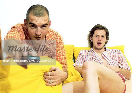 Two men sitting on sofa, one pointing remote control at camera Stock Photo - Premium Royalty-Free, Image code: 695-03385900