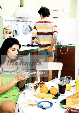 Woman sitting at breakfast table, man standing, scratching rear Stock Photo - Premium Royalty-Free, Image code: 695-03385925