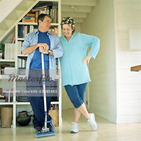 Mature couple standing side by side, man holding broom Stock Photo - Premium Royalty-Free, Image code: 695-03385983
