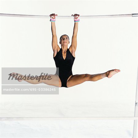 Young female swinging on uneven bars Stock Photo - Premium Royalty-Free, Image code: 695-03386245