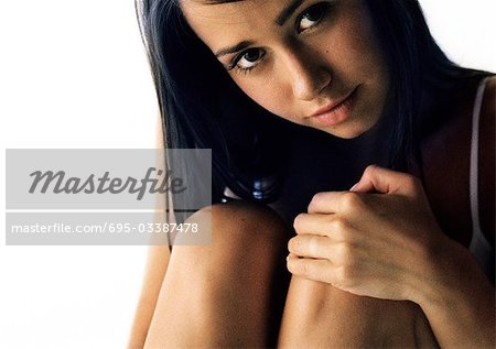 Woman hugging knees, looking at camera, close up Stock Photo - Premium Royalty-Free, Image code: 695-03387478