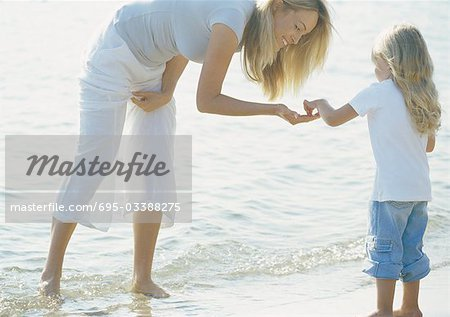 Mother holding hand out to girl on beach Stock Photo - Premium Royalty-Free, Image code: 695-03388275