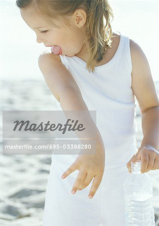 Girl licking water off arm on beach Stock Photo - Premium Royalty-Free, Image code: 695-03388280