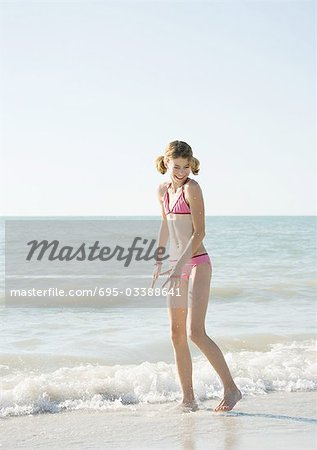 Girl standing in surf on beach Stock Photo - Premium Royalty-Free, Code: 695-03388641