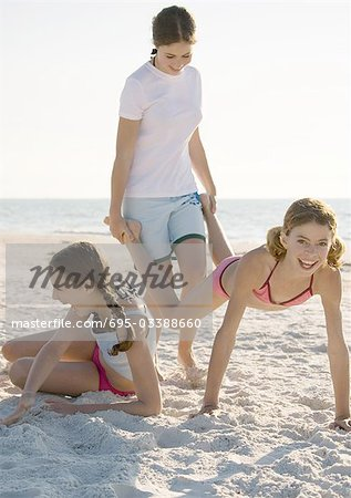 Three girls on the beach, one holding the other's legs like wheelbarrow Stock Photo - Premium Royalty-Free, Image code: 695-03388660