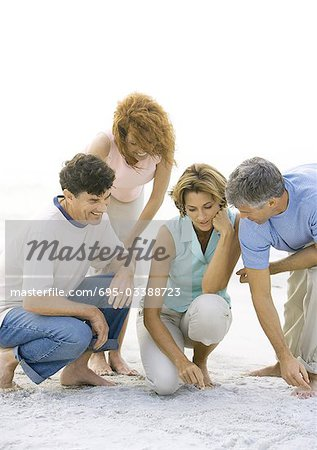 Two mature couples crouching on beach Stock Photo - Premium Royalty-Free, Image code: 695-03388723