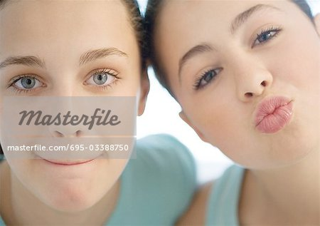 Two preteen girls, one puckering, the other pursing lips