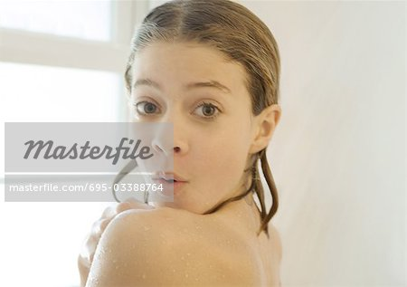 Preteen girl in shower, looking over shoulder at camera