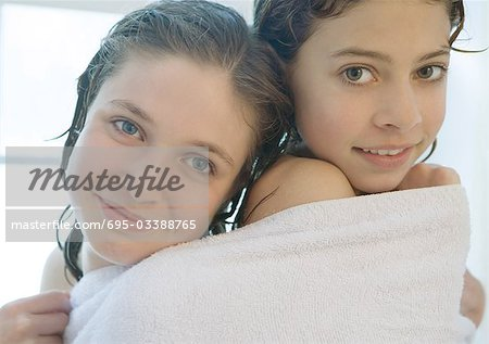 Two preteen girls sharing towel