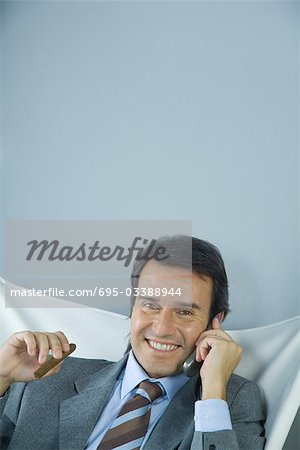 Businessman using cell phone and holding cigar, smiling at camera Stock Photo - Premium Royalty-Free, Image code: 695-03388944