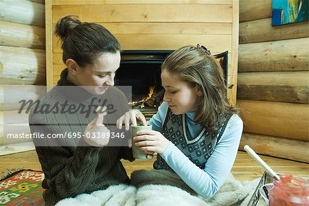 Two teenage girls sitting by fireplace, sharing snack Stock Photo - Premium Royalty-Free, Image code: 695-03389346