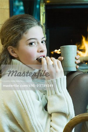 Teenage girl sitting next to fireplace, eating snack, looking at camera Stock Photo - Premium Royalty-Free, Image code: 695-03389349