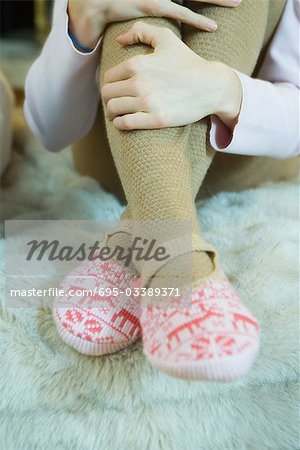 Teenage girl hugging knees, wearing tights and slippers, cropped view of legs Stock Photo - Premium Royalty-Free, Image code: 695-03389371