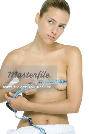 Woman holding measuring tape around chest, looking away Stock Photo - Premium Royalty-Free, Image code: 695-03389815