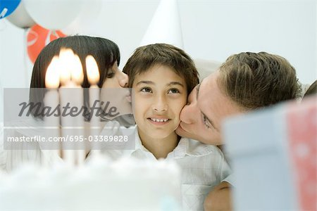 Family behind birthday cake with lit candles, parents kissing boy on cheeks Stock Photo - Premium Royalty-Free, Image code: 695-03389828