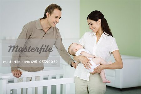 Parents standing in nursery, woman holding sleeping baby Stock Photo - Premium Royalty-Free, Image code: 695-03390060