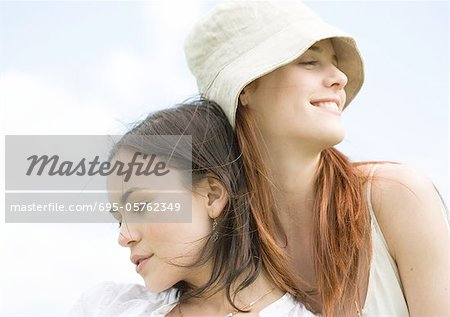 Two young women, leaning on each other with eyes closed Stock Photo - Premium Royalty-Free, Image code: 695-05762349