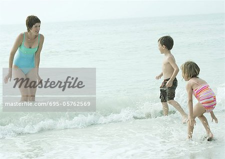 Family at the beach, mother standing in the waves looking at children coming into water Stock Photo - Premium Royalty-Free, Image code: 695-05762569