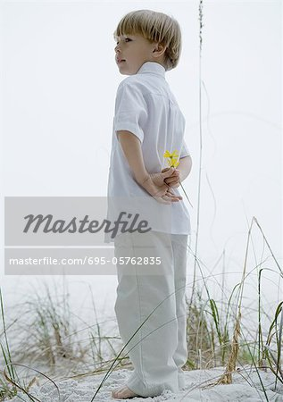 Little boy standing in dunes, holding flowers behind back Stock Photo - Premium Royalty-Free, Image code: 695-05762835