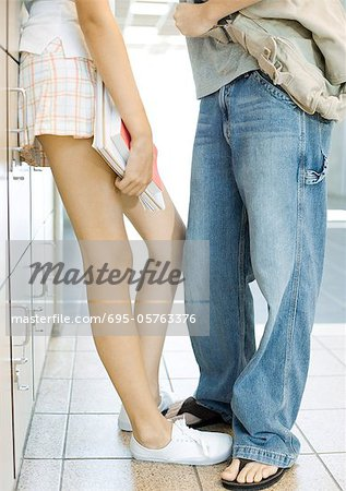 Teen couple leaning against school lockers, waist down Stock Photo - Premium Royalty-Free, Image code: 695-05763376