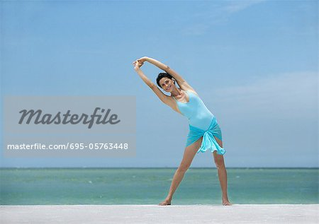 Woman stretching on beach Stock Photo - Premium Royalty-Free, Image code: 695-05763448