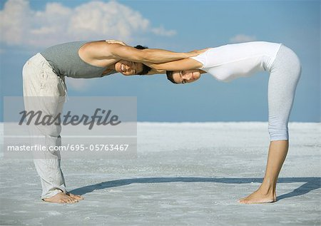 Man and woman bending over, head to head, arms together, on beach Stock Photo - Premium Royalty-Free, Image code: 695-05763467