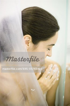 Woman in shower, washing shoulder Stock Photo - Premium Royalty-Free, Image code: 695-05765401