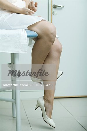 Woman sitting on examination table, crossing legs nervously, waist down Stock Photo - Premium Royalty-Free, Image code: 695-05765439