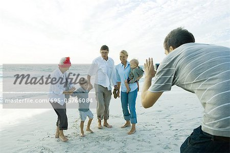 Family on beach, man taking photo Stock Photo - Premium Royalty-Free, Image code: 695-05766084