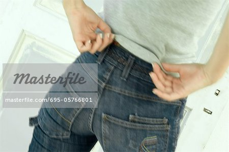 Woman untucking shirt from waist of jeans, close-up, rear view Stock Photo - Premium Royalty-Free, Image code: 695-05766801