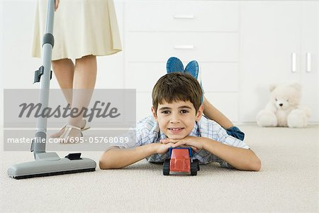 Little boy lying on the ground with toys, smiling at camera, mother vacuuming around him Stock Photo - Premium Royalty-Free, Image code: 695-05768089