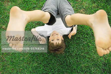 Boy lying on grass with legs in air, overhead view Stock Photo - Premium Royalty-Free, Image code: 695-05768146