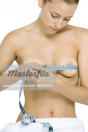 Nude woman measuring breasts with measuring tape, looking down Stock Photo - Premium Royalty-Free, Image code: 695-05768232