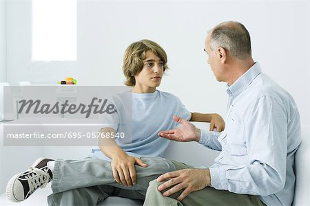 Father and teen son sitting together on sofa, having discussion Stock Photo - Premium Royalty-Free, Image code: 695-05768540