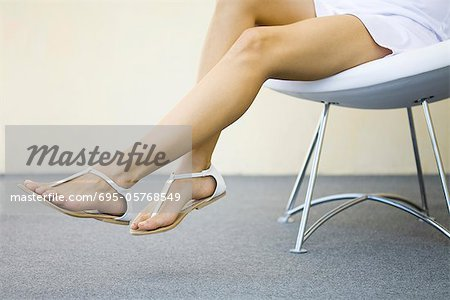 Woman sitting in chair with legs dangling, wearing sandals, cropped view