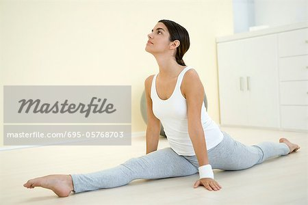 Young woman doing splits, looking up Stock Photo - Premium Royalty-Free, Image code: 695-05768703