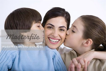 Portrait of smiling mother being kissed on each cheek by daughter and son Stock Photo - Premium Royalty-Free, Image code: 695-05769086