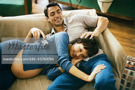 Expecting couple relaxing on sofa, watching TV, woman resting head in man's lap Stock Photo - Premium Royalty-Free, Image code: 695-05769765