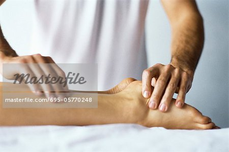 Therapist treating patient's foot with acupressure Stock Photo - Premium Royalty-Free, Image code: 695-05770248
