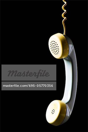 Telephone receiver hanging by cord Stock Photo - Premium Royalty-Free, Image code: 695-05770356