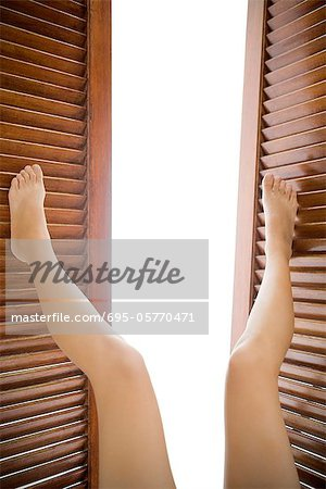 Legs pushing open wooden shutters Stock Photo - Premium Royalty-Free, Image code: 695-05770471
