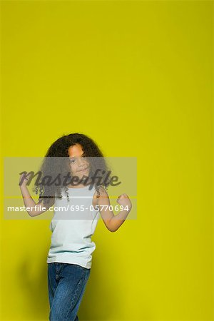 Little girl flexing muscles, portrait Stock Photo - Premium Royalty-Free, Image code: 695-05770694